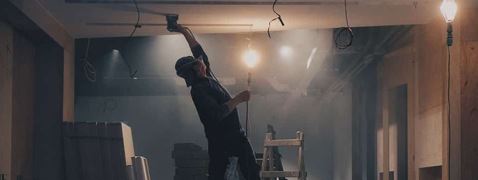 worker putting up drywall inside of a house